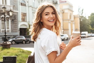 Woman smiling in city holding coffee