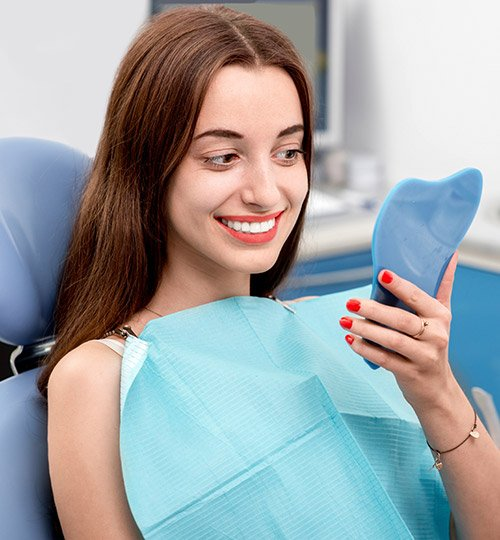 Young woman in dental chair examining smile in mirror