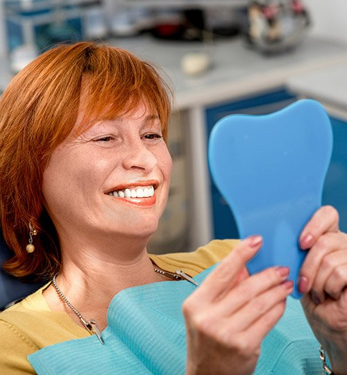 Senior woman examining her restored smiled