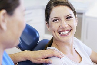 Relaxed woman laughing in dental chair